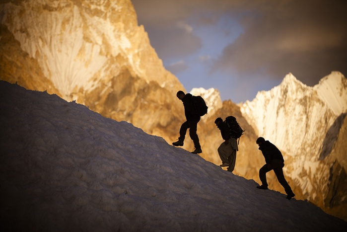 7. Expedition members meander between crevasses with the Gasherbrum IV massif visible in the background