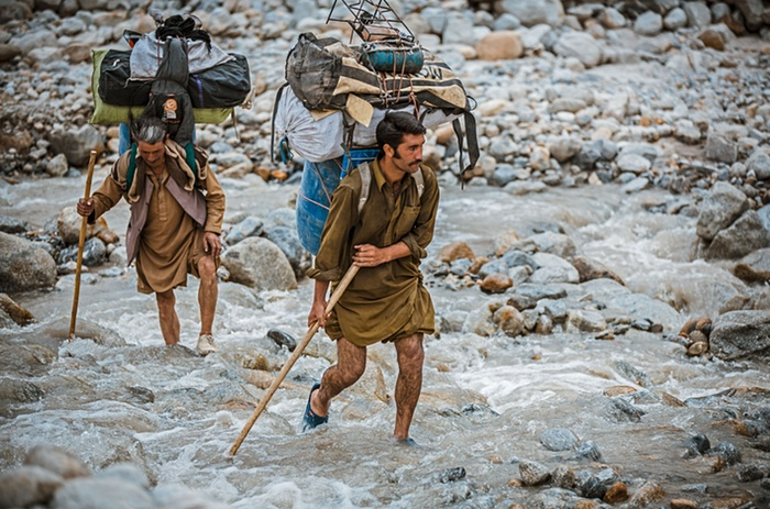 9. Balti porters carrying loads which range from 25kg to 50kg, a task they undertake often wearing only basic rubber sneakers filled with fresh grass to stop their feet sli